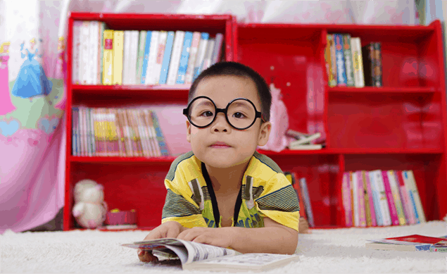 young asian boy wearing oversized glasses in classroom