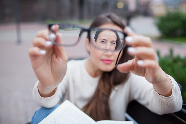 girl with myopia holding glasses in front of her face
